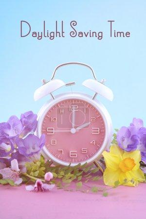 Photo pour Concept d'heure d'été printanier avec horloge rose sur table en bois rose avec fond bleu ciel, avec exemple de texte . - image libre de droit