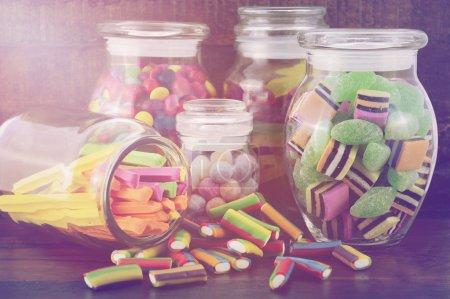 Photo pour Happy Halloween Candy en verre apothicaire pots sur table en bois sombre, avec des filtres vintage rétro ajoutés et éclat de lentille de flux de lumière . - image libre de droit