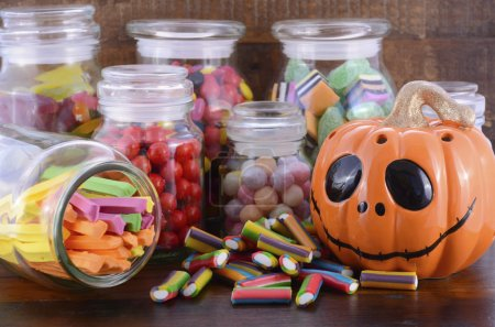 Photo pour Happy Halloween Candy in Glass Apothecary Jars with orange pumpkin Jack O Lantern closeup on dark wood table. - image libre de droit
