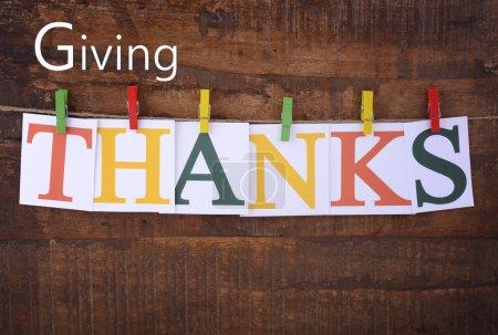 Photo pour Thanksgiving partie bunting sur fond de bois sombre, avec des lettres orthographiant le mot, Merci, accroché à des chevilles colorées sur une ligne . - image libre de droit