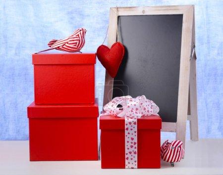 Photo pour Tableau de Saint-Valentin avec des cadeaux tsack rouge et ormanets d'oiseaux sur table en bois blanc et fond bleu . - image libre de droit