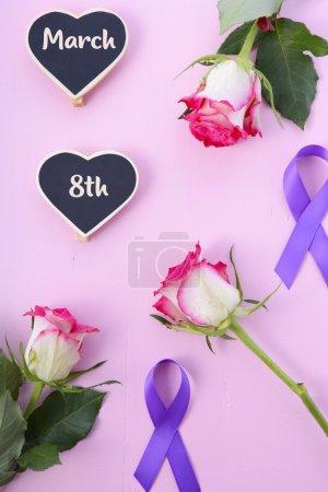 Photo pour Journée internationale de la Womens, le 8 mars, plat poser arrangement de roses et de rubans violets sur fond de table en bois rose - image libre de droit