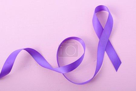 Photo pour Symbole de ruban violet Womens la journée internationale, le 8 mars, sur fond de bois rose avec les souhaits de copie espace et exemple de texte. - image libre de droit