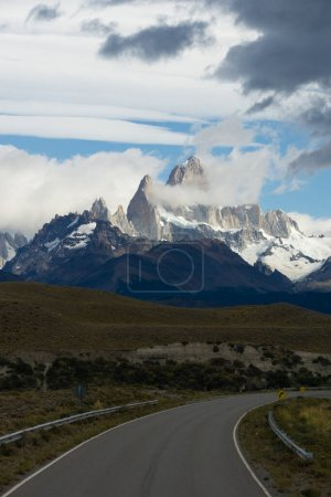 Photo for Asphalted road with the peaks of a rocky and snowy mountain on the horizon. Fitz Roy mountain in Argentina vertical Photograph - Royalty Free Image