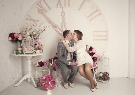 Photo pour Mariée et marié assis sur un banc en couleurs - image libre de droit