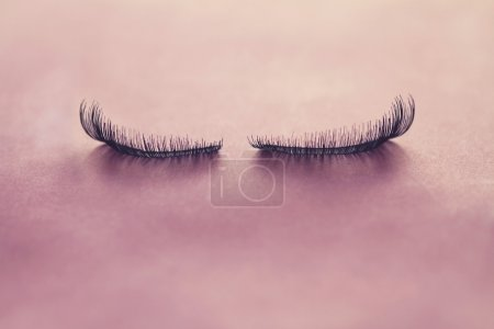 Close up false eyelashes on pink background