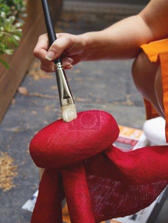 Photo pour Solution de raidissement au brossage Milliner sur un bloc de chapeau rouge - image libre de droit
