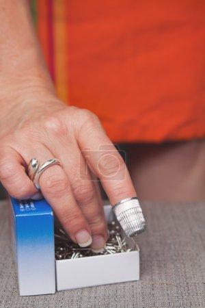 Photo pour Dressmakers mains doigt dé à coudre atteignant dans la boîte de broches - image libre de droit