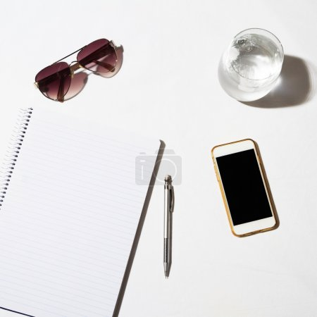 Sunglasses, water, phone and notepad flat lay on a white table