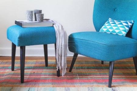 Teal retro armchair and ottoman with decor objects horizontal