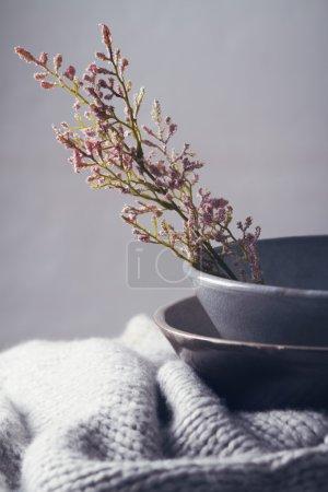 Photo pour Bols vintage gris nature morte avec fleurs roses et une écharpe en laine - image libre de droit