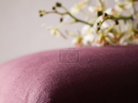Burgundy colored ottman with blurred orchids in background
