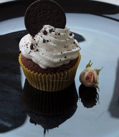 Photo pour Gâteau à la crème blanche décoré de biscuits sur une assiette noire - image libre de droit