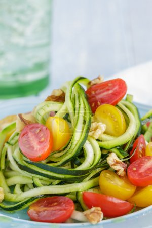 Photo for Zucchini noodles with tomatoes and walnuts tossed in olive oil - Royalty Free Image