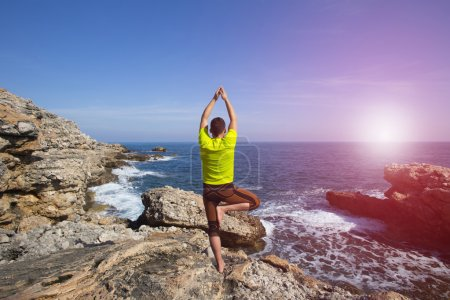 Photo for Young man practicing yoga on the beach. - Royalty Free Image