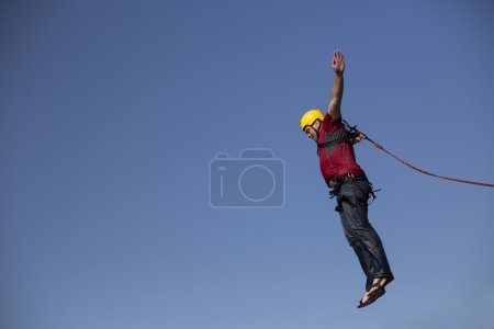 A man jumps from a cliff into the abyss....