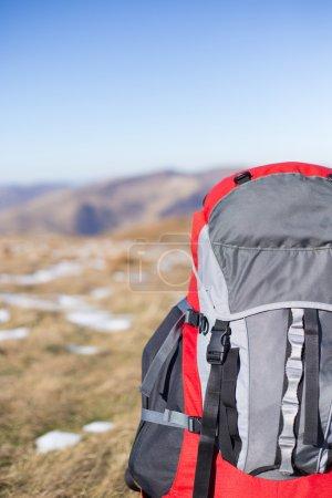 Photo pour Commandes de sac à dos rouge sur le dessus de la montagne. - image libre de droit