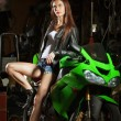 Sexy woman in garage with her sport bike...