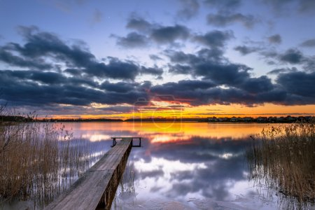 Purple Sunset over Tranquil Lake with Reed and Wooden Jetty
