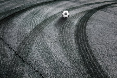 Abstract asphalt tires tracks with soccer ball