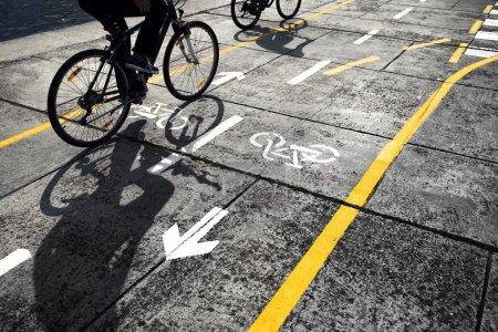 Photo pour Cyclistes suivant une piste cyclable dans la rue. Belle journée ensoleillée avec deux cyclistes aux ombres sur piste cyclable . - image libre de droit