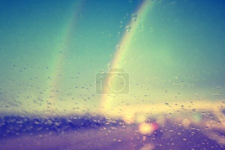 Vintage rainy windshield with rainbows