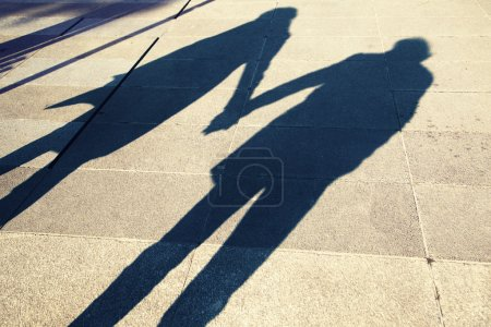 Shadow of two people holding hands on a walk