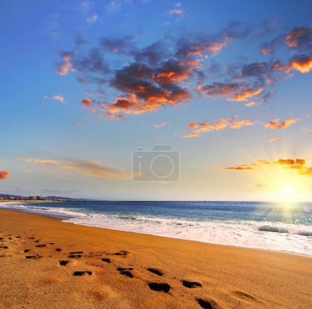 Beach travel - footprints in the sand on beach at sunset. Travel and business background