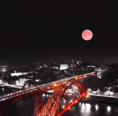 Red moon and Red Bridge on a monochromatic background, night view of the Dom Luiz bridge captured on a slow shutter, Porto , Portugal. Traver concept