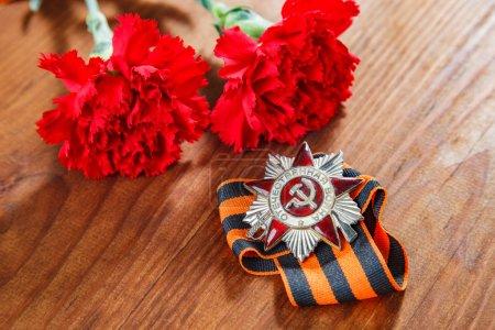 Photo pour Ordre de la guerre patriotique à St. et deux fleurs rouges et un ruban George sur bois - image libre de droit