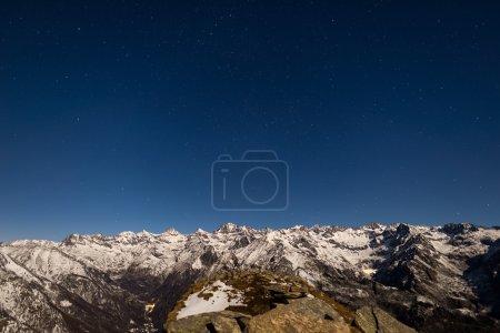 Photo pour Le ciel étoilé capturé sur les Alpes. Le parc national Gran Paradiso a recouvert la chaîne de montagnes enneigées d'un clair de lune. Faible bruit numérique. Italie . - image libre de droit