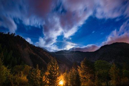 Photo pour Le ciel étoilé avec des nuages de mouvement flous et un clair de lune brillant, capturé dans la forêt de mélèzes, rayonnant par le feu brûlant. Paysage nocturne étendu dans les Alpes européennes. Concept d'aventure dans la nature . - image libre de droit