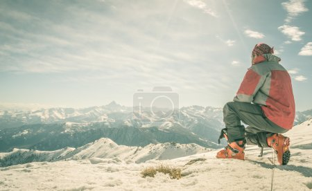 Photo for Alpinist kneeling on the mountain summit. Shot in backlight, stunning panoramic view of the alpine arc. Concept of success and conquering the top. Toned image, old retro touch. - Royalty Free Image
