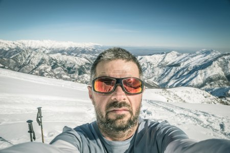 Photo for Adult sport man taking selfie on snowy slope with the beautiful snowcapped italian Alps in the background. Slightly toned and desaturated image. Vignetting applied. - Royalty Free Image