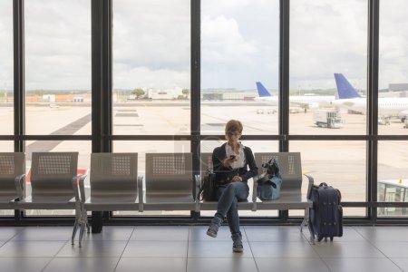 Waiting in airport terminal using phone