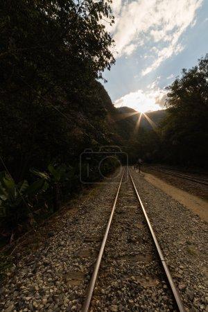 Photo pour La voie ferrée traversant la jungle et reliant le village de Machu Picchu à la centrale hydroélectrique, principalement utilisé à des fins touristiques et du fret. Magnifique coucher de soleil en contre-jour sur la crête. - image libre de droit