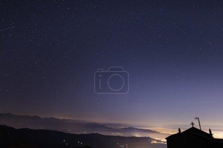 Photo pour Le ciel étoilé sur les Alpes italiennes avec petite silhouette de chapelle. L'Étoile polaire, la Petite Ourse ou Petite Ourse (Ourse Mineure), la constellation de la Grande Ourse (Ourse Majeure) ou la Grande Ourse. Des vallées scintillantes . - image libre de droit