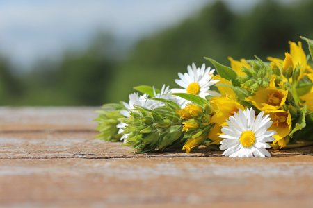 Background for an inscription. Wild flowers on a wooden table in