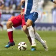 Legs of two soccer players vie on a match...