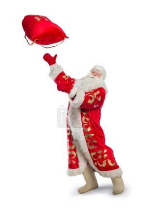 Photo for Santa Claus is standing on the floor and is tossing up the bag of gifts - Royalty Free Image