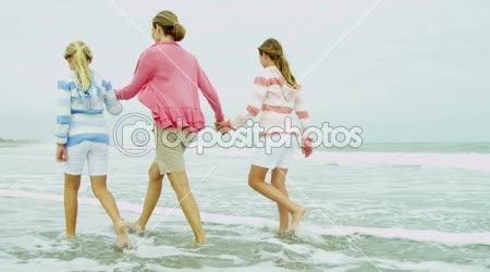 Mother with daughters walking on beach