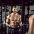 Young adult bodybuilder doing weight lifting in gy...