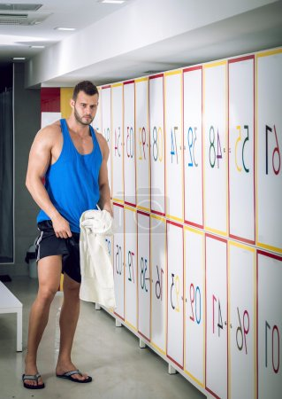 Young man standing in locker room