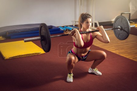 Girl doing squats with weight