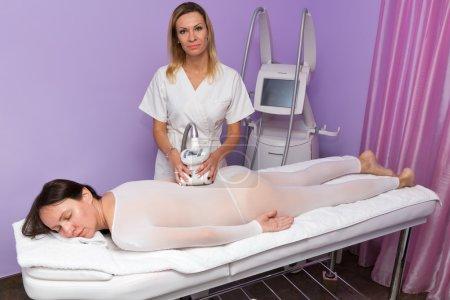 Photo pour Femme dans le costume spécial blanc ayant massage anti-cellulite avec appareil - image libre de droit