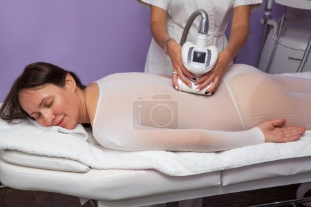 Photo pour Femme dans le costume spécial blanc ayant anti cellulite massage avec appareil - image libre de droit
