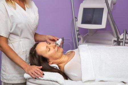 Photo pour Femme ayant massage anti-cellulite sur son visage avec thérapeute et appareil - image libre de droit