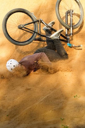 Biker is falling from his bike to the sand