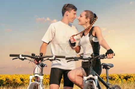 Photo pour Jeune couple heureux amoureux de vélos sportifs sur fond de champ de tournesols - image libre de droit