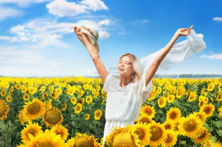Photo for Beautiful joyful woman in blooming sunflower field - Royalty Free Image